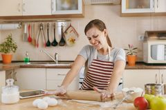 Young beautiful woman is cooking in the kitchen. The young beautiful happy woman sitting at a table with flour and tablet, rolling a dough with a rolling pin Royalty Free Stock Photos