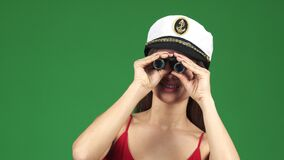 Young beautiful happy woman smiling looking to the camera through binoculars. Close up of a gorgeous happy young woman smiling wearing sailor cap looking to the stock video footage