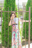 Young beautiful happy woman stands near the lattice fence royalty free stock photos