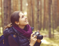 Young, beautiful and happy woman walking in forest and taking pi Stock Image
