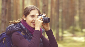 Young, beautiful and happy woman walking in forest and taking pi Stock Photo