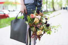 Young beautiful happy woman walking on the street with bag and b. Young beautiful woman walking on the street with bag and bouquet of a flowers. Model wearing Royalty Free Stock Image
