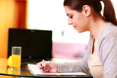 Young beautiful happy woman writing notes Stock Photo