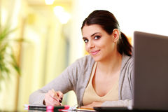 Young beautiful happy woman writing notes Stock Image
