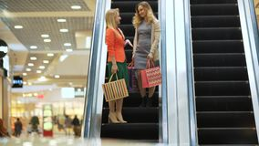 Young beautiful happy women on escalator of shopping mall stock video