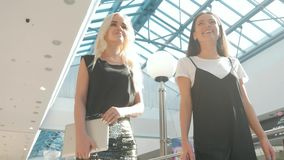 Young beautiful happy women with shopping bags in mall, student girls shopping after lessons, two girls in airport. Young beautiful happy women with shopping stock video