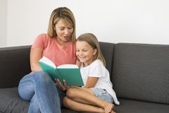 Young beautiful and happy women sitting together with her adorable 7 years old adorable blond girl reading book enjoying telling s Stock Photography