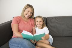 Young beautiful and happy women sitting together with her adorable 7 years old adorable blond girl reading book enjoying telling s Royalty Free Stock Photography