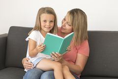Young beautiful and happy women sitting together with her adorable 7 years old adorable blond girl reading book enjoying telling s Stock Photo