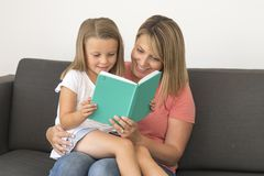 Young beautiful and happy women sitting together with her adorable 7 years old adorable blond girl reading book enjoying telling s Royalty Free Stock Photos