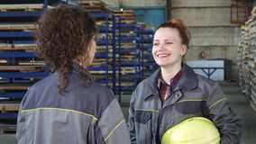Young beautiful hardware storage female worker talking to her colleague