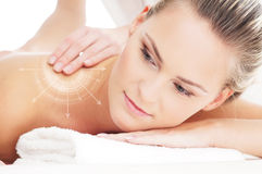 A young, beautiful and healthy woman getting spa treatment. A beautiful, healthy and young woman getting spa massage treatment. (Concept with arrows Royalty Free Stock Photography