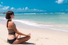 Young beautiful healthy woman making meditation on the beach Nusa Dua, tropical Bali island, Indonesia. Royalty Free Stock Image