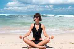 Young beautiful healthy woman making meditation on the beach Nusa Dua, tropical Bali island, Indonesia. Stock Images