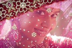 Young beautiful Hindu bride looking through jeweled veil. At camera Stock Photo