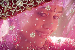 Young beautiful Hindu bride looking through jeweled veil. Young beautiful Hindu bride smiling while looking through jeweled veil Royalty Free Stock Photo