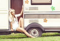 Young and beautiful hippy girl sitting on trailer. Holiday, jour. Young and beautiful hippy girl sitting on trailer at summer. Holiday, journey, vacation concept Royalty Free Stock Photos