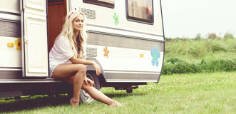 Young and beautiful hippy girl sitting on trailer. Holiday, jour. Young and beautiful hippy girl sitting on trailer at summer. Holiday, journey, vacation concept Royalty Free Stock Image