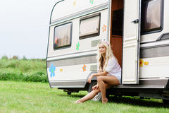Young and beautiful hippy girl sitting on trailer. Stock Image