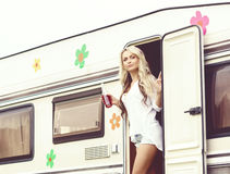 Young and beautiful hippy girl standing in trailer's door. Hol Royalty Free Stock Photography