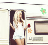 Young and beautiful hippy girl standing in trailer's door. Hol. Young, attractive hippy girl standing in trailer's door with bottle of refreshing drink Royalty Free Stock Image