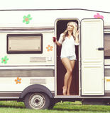 Young and beautiful hippy girl standing in trailer's door. Hol. Young, attractive hippy girl standing in trailer's door with bottle of refreshing drink Stock Photography