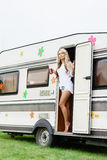 Young and beautiful hippy girl standing in trailer's door. Stock Photos