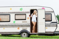 Young and beautiful hippy girl standing in trailer's door. Young and beautiful hippy girl standing in trailer's door. Holiday, journey, vacation concept Royalty Free Stock Photos