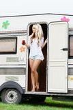 Young and beautiful hippy girl standing in trailer's door. Stock Image