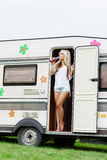 Young and beautiful hippy girl standing in trailer's door. Royalty Free Stock Image