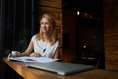 Young beautiful hipster girl with good mood sitting with big notepad in coffee shop during her recreation time, Stock Photos