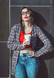 Young beautiful hipster girl in red blouse with cup of coffee Stock Photo