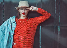 Young beautiful hipster girl in red jersey with hat near wall Stock Photos