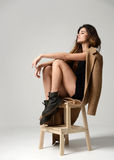 Young beautiful hipster girl sitting on chair thinking in little Stock Image