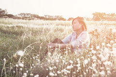 Young beautiful hipster pensive woman sitting on the meadows Royalty Free Stock Images