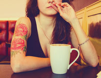 Young beautiful hipster tattooed woman with red curly hair at the bar with cup of coffee Stock Photography