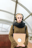 Young beautiful hipster woman in big dj headphones posing with a vinyl records on subway entrance Stock Photography
