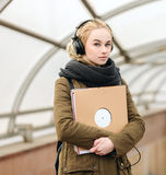 Young beautiful hipster woman in big dj headphones posing with a vinyl records on subway entrance Stock Image