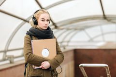 Young beautiful hipster woman in big dj headphones posing with a vinyl records on subway entrance Stock Photos
