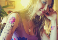 Young beautiful hipster woman with blonde hair and tattoo hands in cafe. Tattoo design in the form pin-up girl with flower head and USA flag. Vintage style Stock Photos