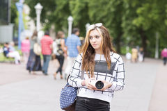 Young beautiful hipster woman with digital camera in the street. Royalty Free Stock Images