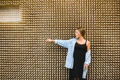 Young beautiful woman against the background of an unusual wooden wall. royalty free stock photography