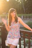 Young beautiful hipster woman greeting somebody at the embankment Royalty Free Stock Image