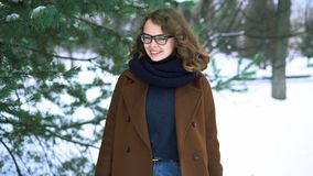 Young beautiful hipster woman in knitted scarf standing in the park and smiling. Winter fashion