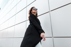 Young beautiful hipster woman in a vintage long black coat in fashionable sunglasses goes on a warm spring day. Near a modern building. Stylish attractive girl royalty free stock photos