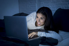 Young beautiful hispanic woman on bed at home laughing happy on laptop computer at night Stock Photo