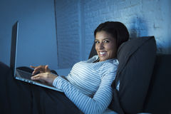Young beautiful hispanic woman on bed at home laughing happy on laptop computer at night Royalty Free Stock Images