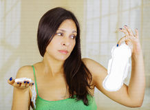 A young beautiful hispanic woman with a green blouse is holding a hygienic towel with one hand and one tamp with her. Other hand, in the bathroom before use it stock photos