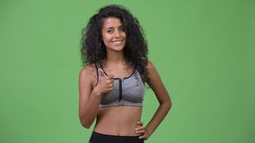 Young beautiful Hispanic woman with gym clothes giving thumbs up