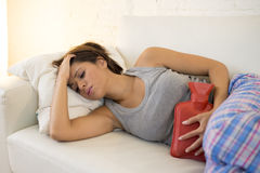 Young beautiful hispanic woman holding hot water bottle against belly suffering menstrual period pain Stock Photography